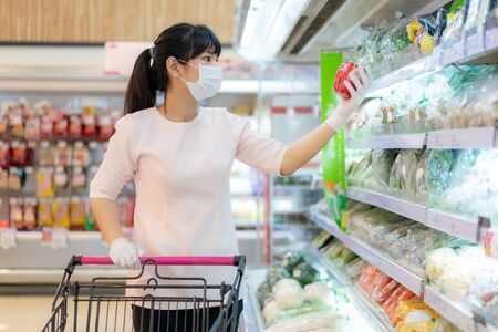 Asian woman with hygienic mask and rubber glove with shopping cart in grocery and looking for fresh vegetable pack to buy during covid-19 outbreak for preparation for a pandemic quarantine