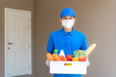 Asian delivery man wearing face mask and glove with groceries box of food, fruit, vegetable and drink standing in front of the customer house during time of home isolation.
