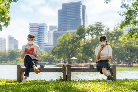Asian young man and woman reading book and chatting in smartphone and wearing mask sitting distance of 6 feet distance protect from COVID-19 viruses for social distancing for infection risk at park