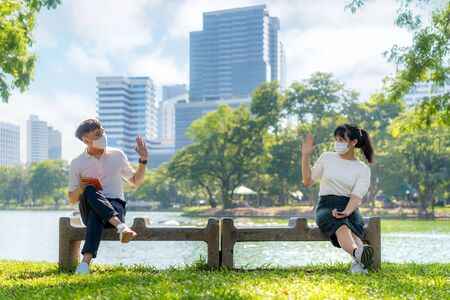 Asian young man and woman greet and say hello with they friend and wearing mask sitting distance of 6 feet distance protect from COVID-19 viruses for social distancing for infection risk in park.