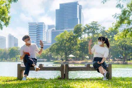 Asiatische junge Männer und Frauen begrüßen und begrüßen ihren Freund und tragen eine Maske mit einem Abstand von 6 Fuß zum Schutz vor COVID-19-Viren zur sozialen Distanzierung für Infektionsrisiken im Park.