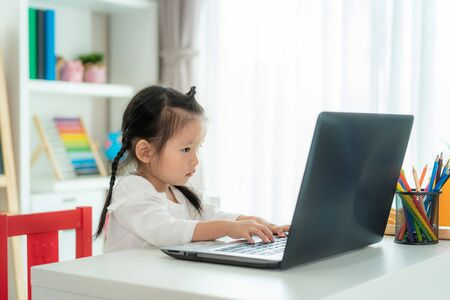 Asian kindergarten school girl video conference e-learning with teacher on laptop in living room at home. Homeschooling and distance learning ,online ,education protect from COVID-19 virus.