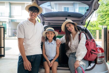 Portrait of Asian family with father, mother and daughter looks happy while preparing suitcase into a car for holiday. Shot in the house garage. 版權商用圖片 - 147496407