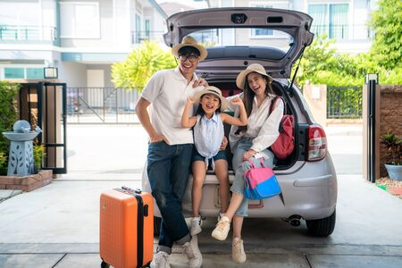 Portrait of Asian family with father, mother and daughter looks happy while preparing suitcase into a car for holiday. Shot in the house garage.