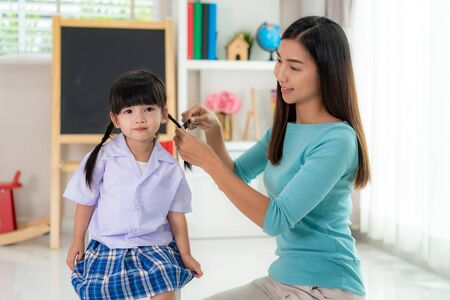 Asian mother Braiding her daughters hair sitting on chair, smiling single mom sister helping child girl with hairstyle at home getting ready to school, family care, morning preparations lifestyle concept Banco de Imagens