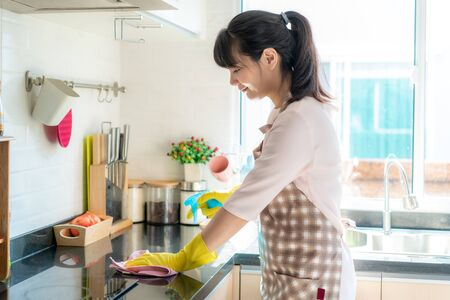 Asian woman wearing rubber protective gloves cleaning kitchen cupboards in her home during Staying at home using free time about their daily housekeeping routine.