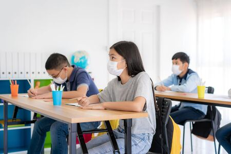Group of Asian elementary school students wearing hygienic mask to prevent the outbreak of Covid 19 in classroom while back to school reopen their school, New normal for education concept.