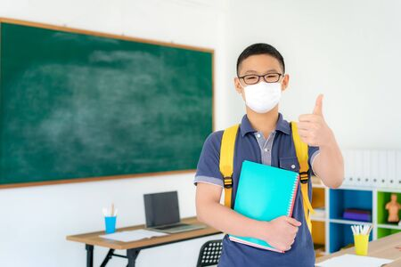 Asian primary students boy thumb up and  wearing masks to prevent the outbreak of Covid 19 in classroom while back to school reopen their school, New normal for education concept.