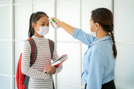Asian woman teacher using thermometer temperature screening student for fever against the spread of COVID-19 while student coming back to school, New normal and Education concept.