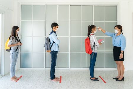 Three Asian student wearing mask standing distance of 6 feet from other people keep distance while teacher using thermometer temperature screening student for fever while student coming back to school.
