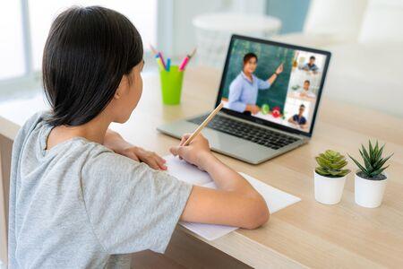 E-learning de vidéoconférence étudiante asiatique avec enseignant et camarades de classe sur ordinateur dans le salon à la maison. Enseignement à domicile et à distance, en ligne, éducation et internet. Banque d'images