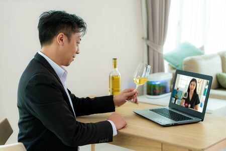 Asian man virtual happy hour meeting party and drinking white grape wine online together with his friend in video conference with digital tablet for a online meeting in video call for social distancing.