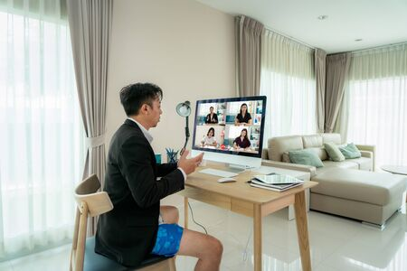 Mixed race businessman wearing Formalwear business suit on top and boxer pants on bottom, showing other people on screen in formal fridays business outfits meeting online in living room at home.