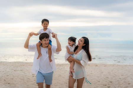 Happy Asian family holidays during joyful father, mother, son and daughter walking together along summer sunset sea. Happy family travel on beach in holiday, Summer and vacation.