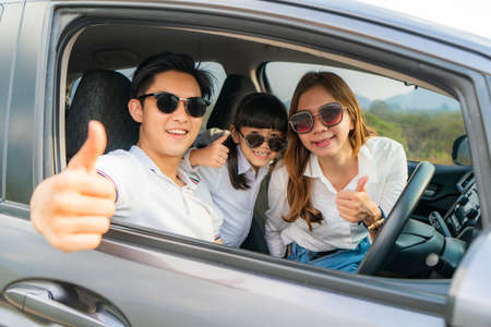 Happy Asian family with father thumb up and mother and daughter wear sunglass in compact car are smiling and driving for travel on vacation. Car insurance or rental Stockfoto