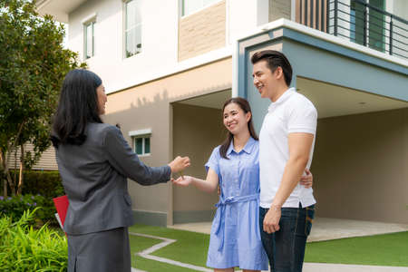 Asian happy smile young couple take keys new big house from real estate agent or realtor in front of their house after signing contract agreement, concept for real estate, moving home or renting property