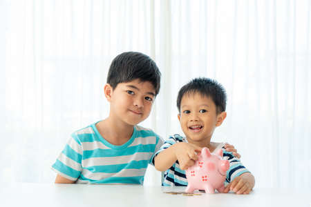 Two Asian cute brother and son insert coin in piggy bank together on the table in living room at home. Concept of bonding of sibling, friendship and saving, investment money for his business future concept