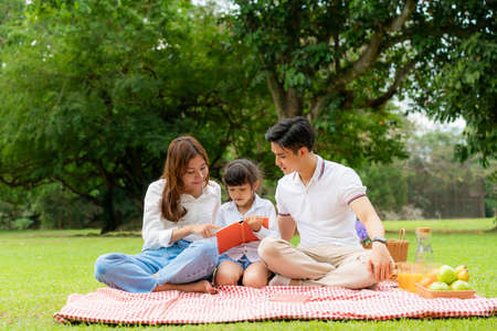 Asian teen family happy holiday picnic moment in the park with father, mother and daughter reading book togerter in green garden with fruit and food. Stock Photo