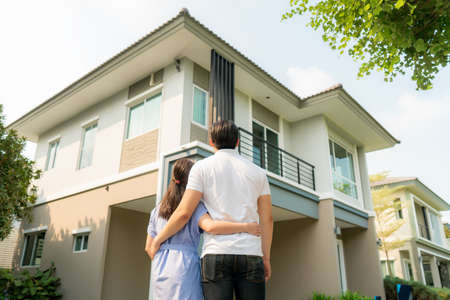Back portrait of Asian young couple standing and hugging together looking happy in front of their new house to start new life. Family, age, home, real estate and people concept.