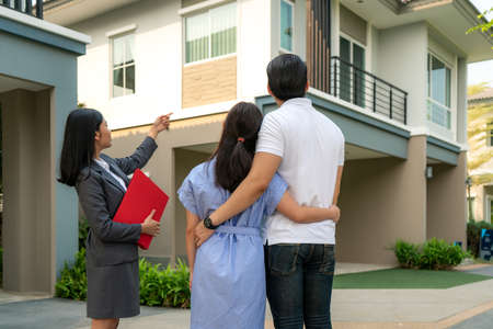 Asian woman Real estate broker agent showing a house project detail in her file to the young Asian couple lover looking and interest to buy it. Buying a new house.
