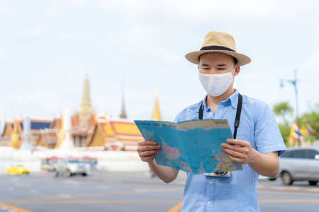 Asian man happy tourists to travel wearing mask to protect from Covid-19 on his holidays and he looking at travel map in Wat Phra Kaew Temple in Bangkok, Thailand Stock Photo