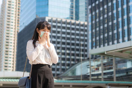 Young Asian businesswoman in white shirt going to work feeling sick with cough wears protection mask prevent PM2.5 dust, smog, air pollution and COVID-19 with business office building in Bangkok, Thailand.