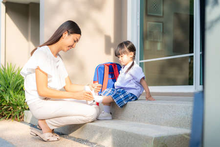 Asian mother helping her daughter put shoes on or take off at outdoor park getting ready to go out together or coming back home from school in happy family with kids concept. Stockfoto