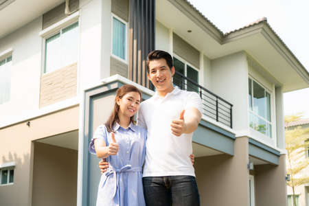 Portrait of Asian young couple standing, hugging and showing thumb up together looking happy in front of their new house to start new life. Family, age, home, real estate and people concept.