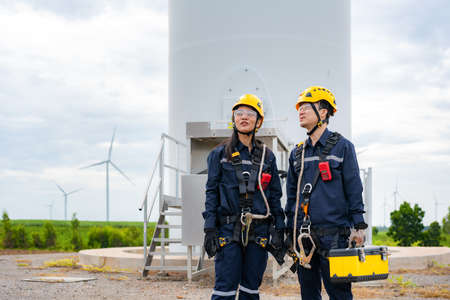 Asian man and woman Inspection engineers preparing and progress check of a wind turbine with safety in wind farm in Thailand. Stock Photo