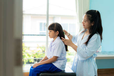 Asian Mother is combing her daughter's hair on the morning before going to school in living room at home. The morning school routine for day in the life getting ready for school