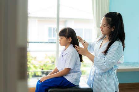 亚洲母亲梳理她的女儿的头发在早上上学前,在家里的客厅。早上学校的日常生活为上学做准备