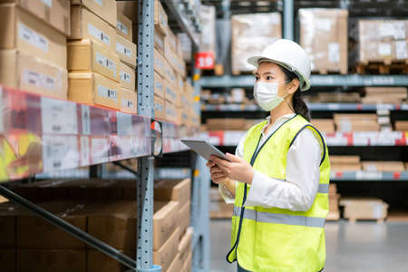 Young asian woman auditor or trainee staff wears mask working during the COVID pandemic in store warehouse shipping industrial. looking up and checks the number of items store by digital tablet. Banque d'images