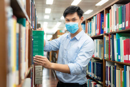 Asian university student boy wearing face protective medical mask for protection from virus disease reading book at library. Education, high school, university, learning and people concept