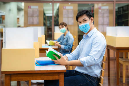 Two Asian university students wearing face mask and sitting and smile in library social distance from other 6 feets to avoid the spread of coronavirus in University.