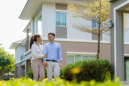 Portrait of Asian couple walking and hugging together looking happy in front of their new house to start new life. Family, age, home, real estate and people concept. Imagens