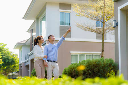 Portrait of Asian couple walking hugging and pointing together looking happy in front of their new house to start new life. Family, age, home, real estate and people concept.