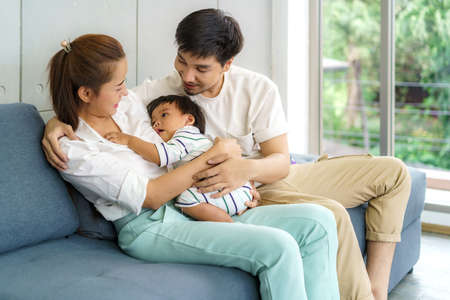 Asian father and mother are hugging 9 months baby son on sofa. They are smiling and warm touching to the baby with love in living room at home