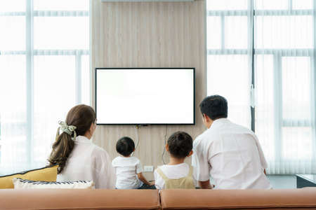 Asian happy family sitting and watching television in living room at home and spent quality time together for activity in vacation day, holiday, happiness or lifestyle concept.