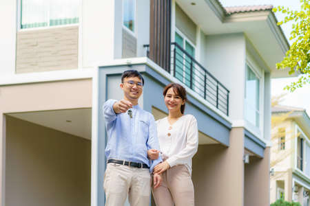 Portrait of Asian young couple standing and hugging together and holding house key looking happy in front of their new house to start new life. Family, age, home, real estate and people concept. Stock Photo