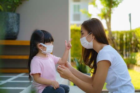 Asian mother help her daughter wearing protection mask to protect the coronavirus Covid-19 outbreak situation before go to school. Get ready to school concept.