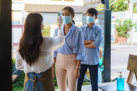 Asian woman cafe employee take temperature Asian woman with face mask before go to restaurant or coffee cafe for new normal lifestyle coronavirus covid-19 pandemic. Standard-Bild
