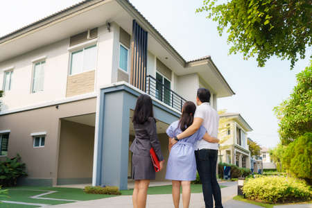 Asian woman Real estate broker agent showing a house detail in her file to the young Asian couple lover looking and interest to buy it. Buying a new house.