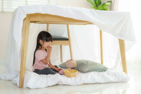 Asian cute little girl eating snack while sitting in a blanket fort in living room at home for perfect hideout away from their other family members and for them to play imaginatively.