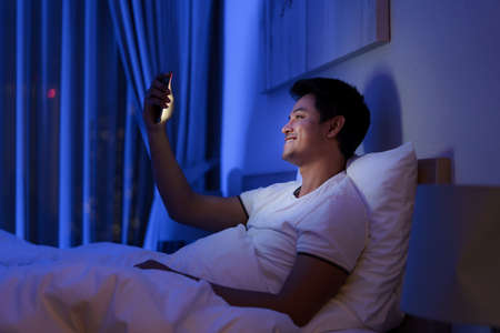 Asian man virtual happy hour meeting online together with his girlfriend in video conference to good night before sleep at night with smartphone for a online meeting in video call