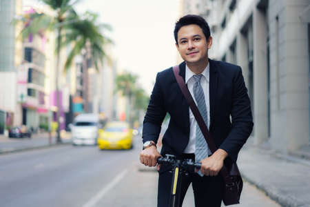 Asian businessman riding an electric scooter on the city streets to go to work in the morning. Daily commute that best reflect the working world of today.