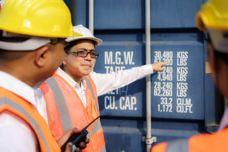 Asian foreman is explaining and teaching new training workers for various components of container to new inspection container worker. Banco de Imagens
