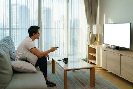An Asian man holds a TELEVISION remote and is pressing the channel while watching TV on the couch in the living room at home.