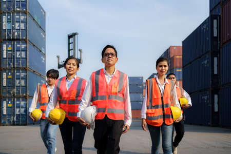 Asian foreman walking with four workers employee team after finishing work on the container depot terminal.