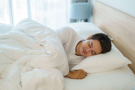 Asian man are sleeping and having good dreams in white blanket in the morning. Rest after work tiring in bedroom at home