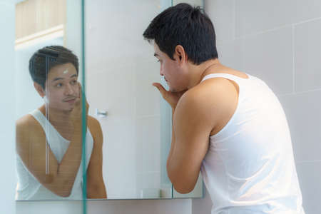 Asian man are applying moisturizer facial cream to his face after bathing and getting ready to work in the bathroom in the house. Banco de Imagens